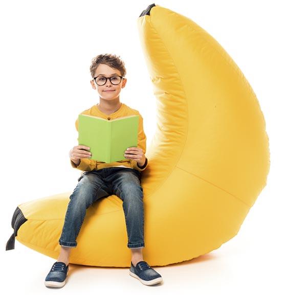 Niño leyendo sobre un plátano hinchable